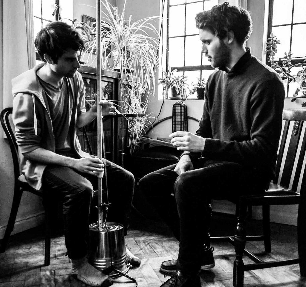 Guy teaches HandleBard Matt Maltby how to play the bucket bass.